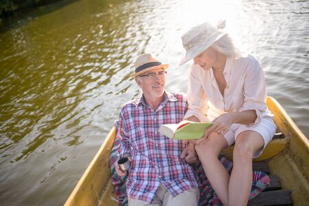 Wife reading book. Wife reading book for husband while having boat trip on the river Stock fotó