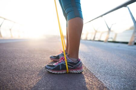 Wearing sneakers. Close up of woman wearing sneakers working out with resistance band