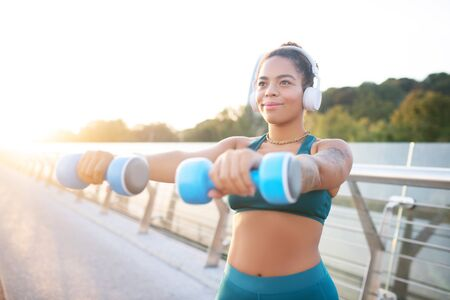 Taking dumbbells. Dark-eyed woman wearing earphones taking dumbbells and building muscles