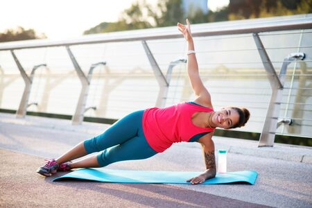 Doing side plank. Smiling African-American woman doing side plank while finishing workout Stock Photo