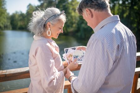 Looking at photos. Happy mature couple having positive emotions while looking at their photos Stok Fotoğraf