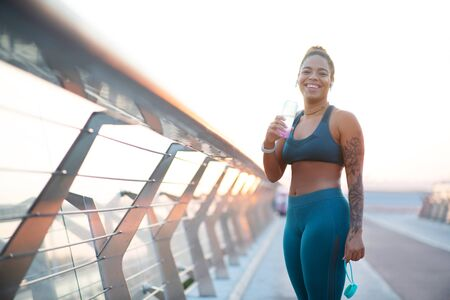 Laughing after running. African-American woman laughing after running in the morning while drinking water