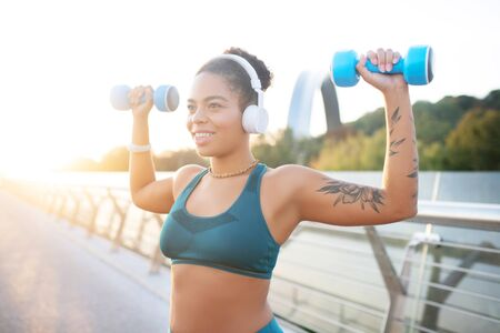 Working out muscles. Dark-skinned woman wearing earphones working out her muscles using barbells