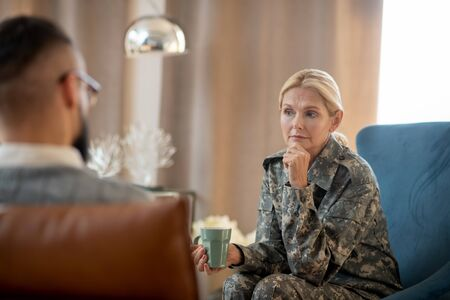 Wearing camouflage uniform. Blonde-haired woman wearing camouflage uniform speaking with psychoanalyst