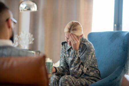 Remembering stressful events. Blonde military woman having headache while remembering stressful events