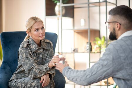 Servicewoman taking water. Servicewoman wearing uniform taking glass of water from psychologist