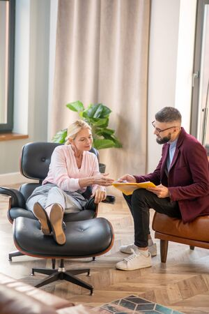 Psychologist assisting. Bearded psychologist wearing glasses assisting woman with her anxiety
