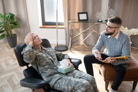 Woman feeling anxious. Bearded psychologist wearing glasses looking at military woman feeling anxious