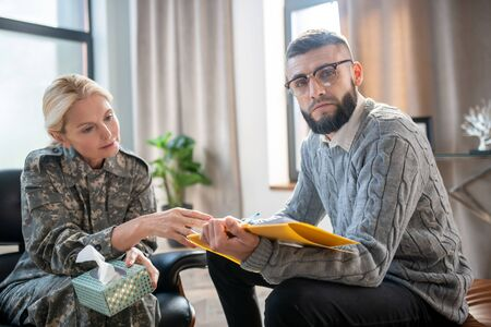 Helping servicewoman. Bearded psychoanalyst wearing glasses helping servicewoman with anxiety Stok Fotoğraf