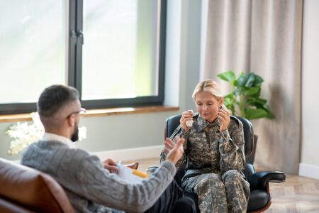 Involved in conversation. Blonde servicewoman involved in conversation with psychoanalyst Stok Fotoğraf