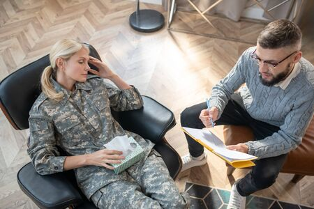 Speaking with servicewoman. Top view of psychologist wearing sweater speaking with servicewoman Stok Fotoğraf