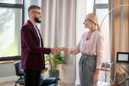 Shaking hand. Stylish mature businesswoman coming to psychologist shaking his hand Stok Fotoğraf