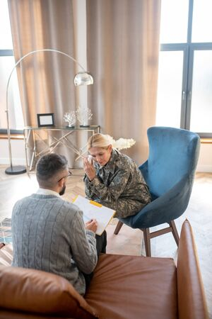 Woman and psychologist. Top view of military woman and psychologist sitting in spacious office Stok Fotoğraf