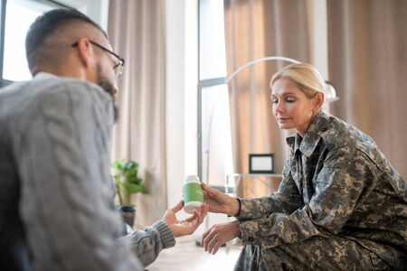 Antianxiety pills. Bearded psychologist giving antianxiety pills for military woman