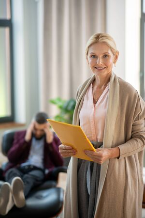 Beautiful psychologist. Beautiful mature psychologist holding documents and standing in her office Stok Fotoğraf