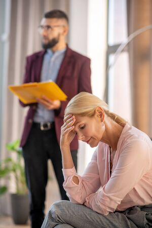 Sharing stress. Blonde-haired woman wearing pink blouse sharing her stress with psychologist Stok Fotoğraf