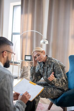 Rehabilitation time. Blonde servicewoman having military rehabilitation and psychoanalysis