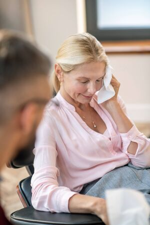 Woman feeling stressed. Blonde mature woman wearing stylish blouse crying while feeling stressed