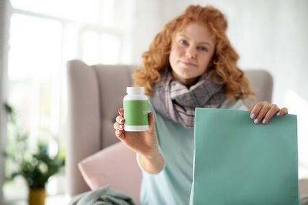 Vitamins in morning. Curly woman feeling relieved after taking vitamins in the morning while having flu