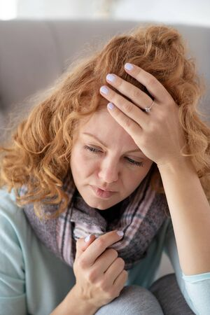 Feeling awfully bad. Red-haired woman feeling awfully bad after catching seasonal epidemical cold