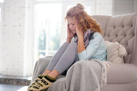Porter des chaussettes chaudes. Femme rousse bouclée portant des chaussettes chaudes souffrant de fièvre et de grippe