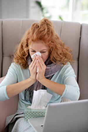 Running nose. Curly sick woman having running nose while watching movie on laptop
