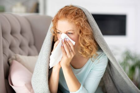 Woman sneezing. Sick red-haired young woman sitting in the living room and sneezing Standard-Bild