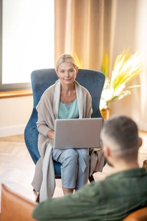 Blonde-haired psychoanalyst. Blonde-haired psychoanalyst holding laptop while listening to patient