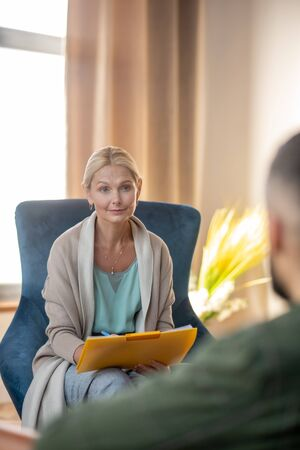 Conversation with patient. Beautiful stylish psychologist involved in having conversation with patient Stok Fotoğraf
