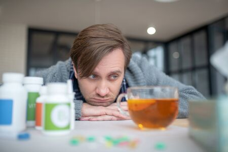 Sick and tired. Blue-eyed man feeling sick and tired drinking hot tea after taking vitamins Stok Fotoğraf
