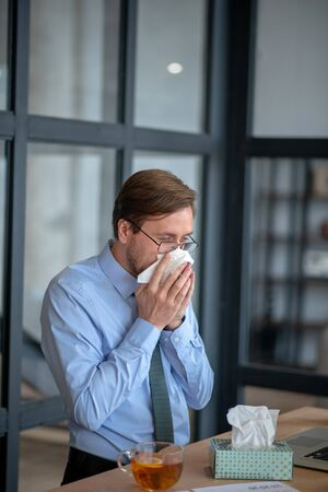 Businessman using napkins. Businessman drinking tea and using napkins while sneezing all day at work
