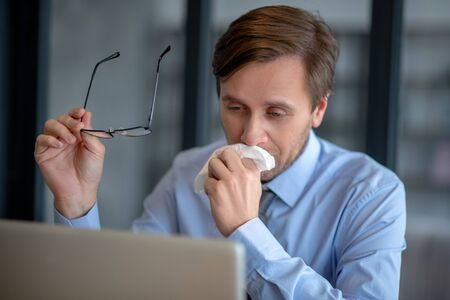 Office despite flu. Businessman wearing blue shirt sitting in the office despite flu Stock Photo