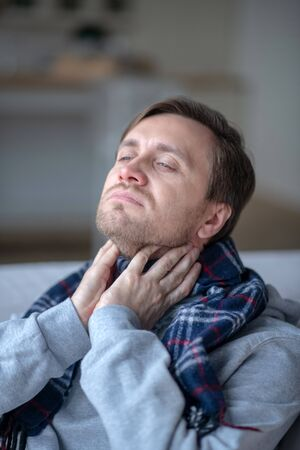 Sick and cold. Sick dark-haired man wearing scarf while feeling sick and cold