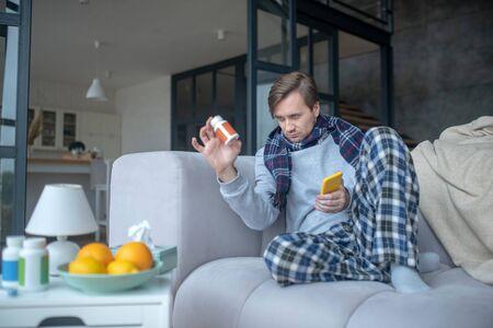 Man holding vitamins. Sick man wearing scarf and pajamas holding pack of vitamin C