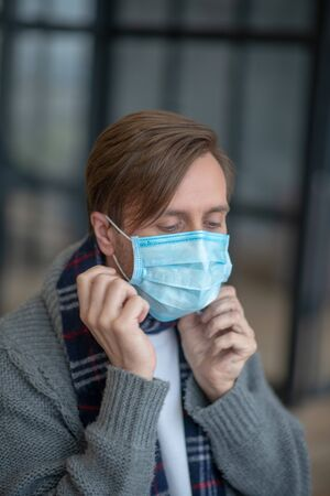 Mask on. Sick and tired dark-haired man putting mask on while caring about his family