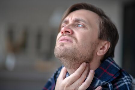 Having awful pain. Blue-eyed man having awful pain in neck while suffering from flu