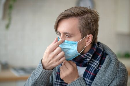 Having infection. Sick mature blue-eyed man wearing mask while having infection