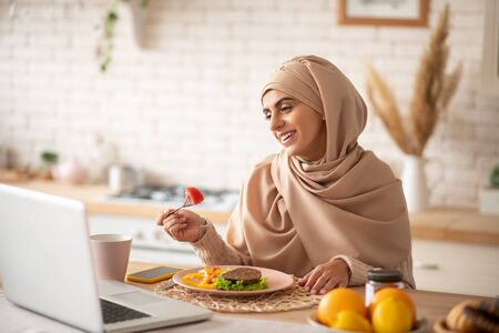 Balanced dinner. Muslim girl enjoying a healthy balanced dinner while watching funny videos on her laptop