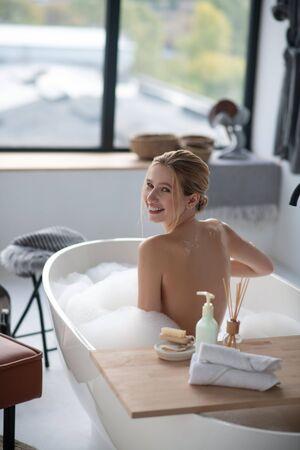 Enjoying foamy bath. Young slim woman smiling while enjoying foamy bath in the morning
