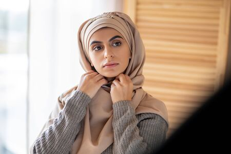 Looking into mirror. Beautiful Muslim girl wearing hijab looking in the mirror Banque d'images