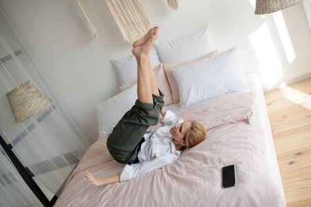 Chilling on bed. Cheerful blonde woman wearing white shirt chilling on bed enjoying day off Banque d'images