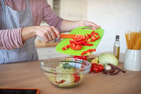 Adding red pepper. Close up of man adding yummy red pepper into vegetable salad while cooking Stock fotó