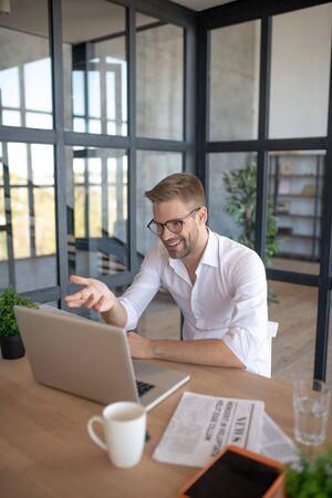 Geschäftsmann nahe Laptop. Geschäftsmann, der morgens Video-Chat mit der Sekretärin hat, während er zu Hause sitzt Standard-Bild