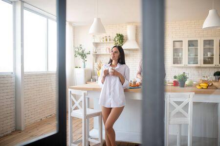 Esposa delgada de piernas largas. Esposa delgada de piernas largas con camisa blanca tomando café por la mañana