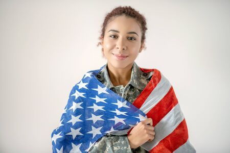 Patriotic servicewoman. Beautiful patriotic servicewoman feeling good while holding American flag