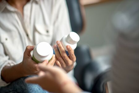 Antidepressants and pills. Close up of woman holding antidepressants and sleeping pills while coming to psychologist