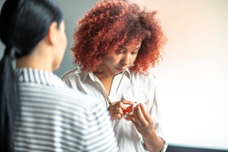 Description of antidepressants. Curly stressed woman reading description of antidepressants while speaking with psychoanalyst Фото со стока