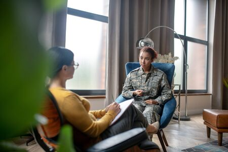 Having military rehabilitation. Servicewoman having military rehabilitation while speaking with psychoanalyst