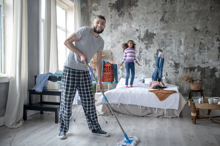 Cleaning the bedroom. Cheerful young man cleaning the bedroom while daughters having fun Stockfoto - 133371979