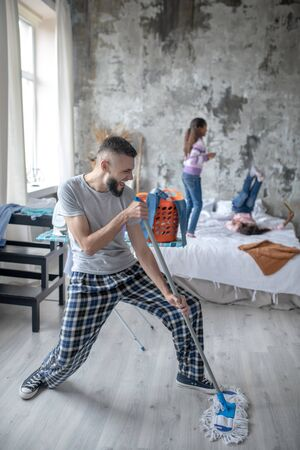 Having much fun. Young father having much fun while mopping floor and daughters playing Stockfoto